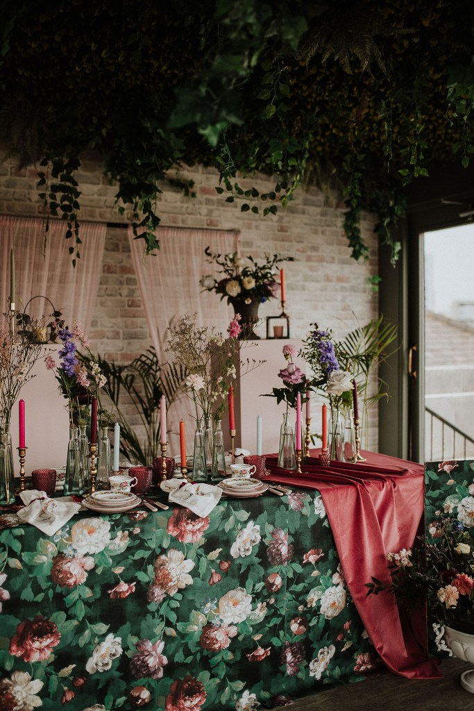 The wedding tablescape was jaw-dropping, with a floral tablecloth, pink runners, colorful candles, burgundy glasses and floral mugs