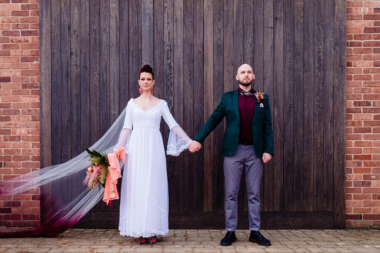 The second groom's look was done with grey pants, a purple shirt, a bright tropical bow tie and a teal blazer