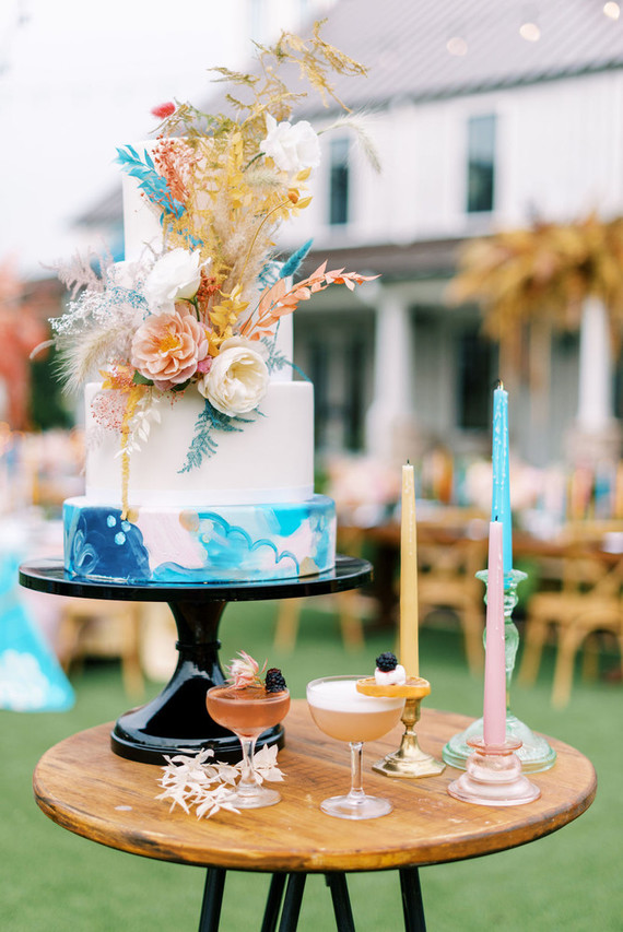 The wedding cake was done with bold watercolors and bright blooms and grasses to finish off the palette of the shoot