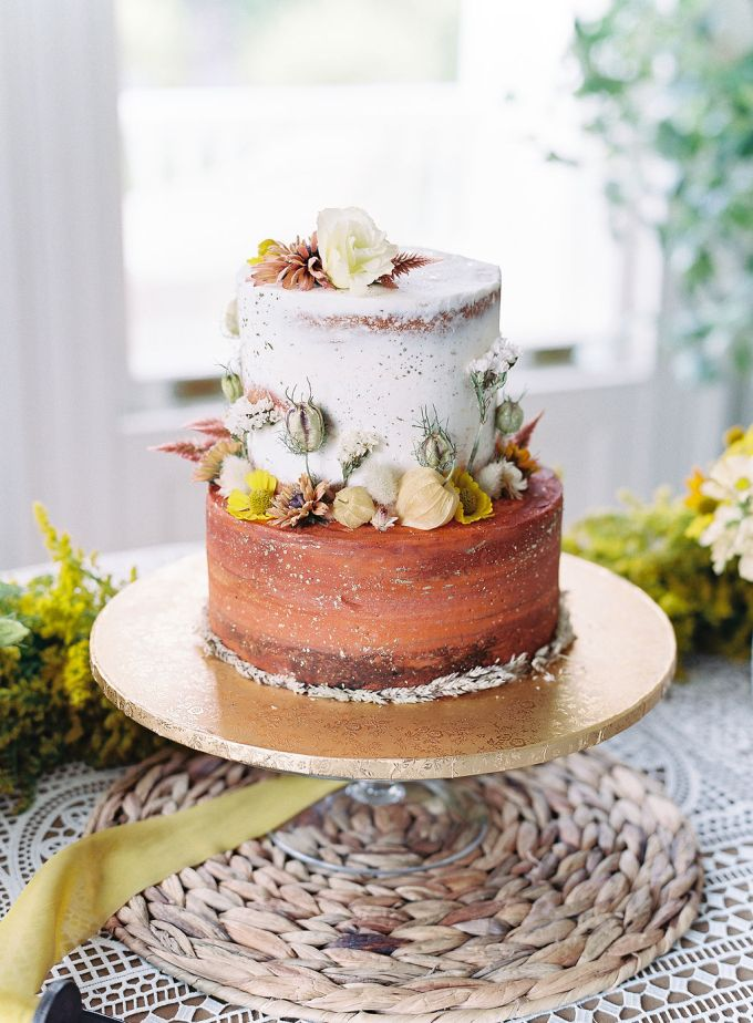 The wedding cake was partly naked and decorated with bright fresh and dried flowers and foliage