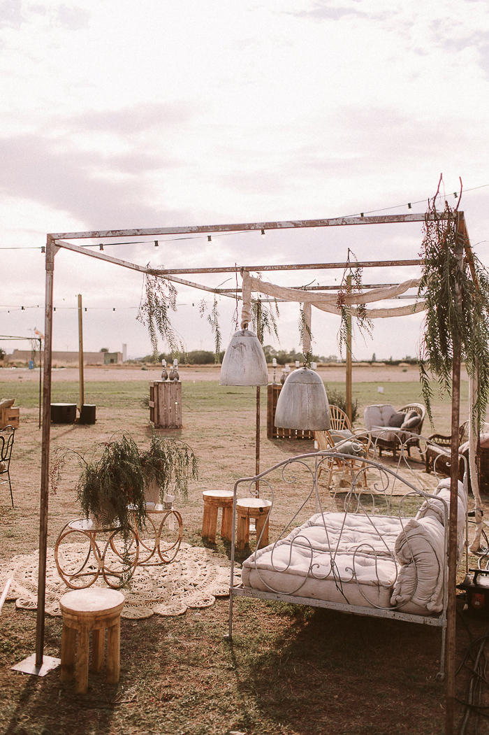 The wedding lounge was done neutral, vintage and boho, with a refined daybed, some pendant lamps, burlap and jute rugs, greenery and wooden stools