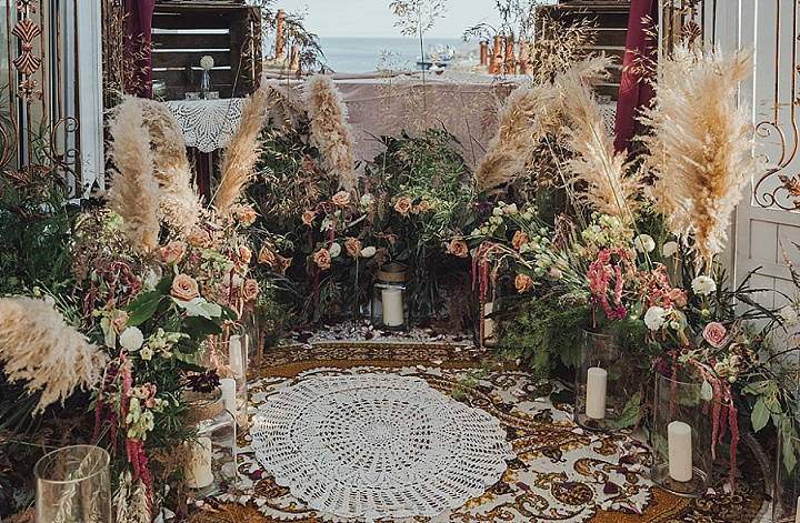 A rooftop was turned into a lush blooming boho space with blush, burgundy and peachy flowers, pampas grass, greenery and candles