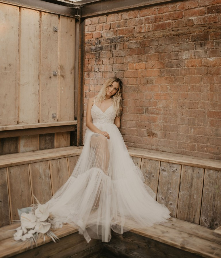 The bride was wearing an A-line spaghetti strap wedding dress with an embellished bodice