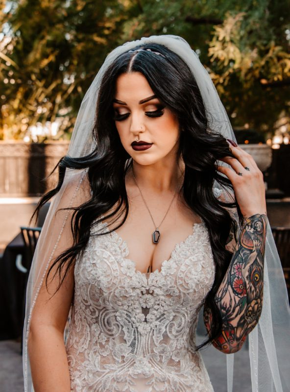 The bride was wearing an embellished lace mermaid wedding dress with a deep neckline, a veil, an embellished headpiece and statement accessories