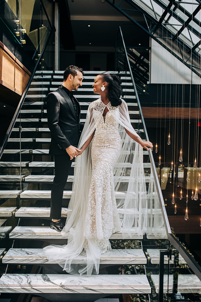 The first bridal look was done with a mermaid lace applique wedding dress and a lovely cape, the groom was wearing a total black look