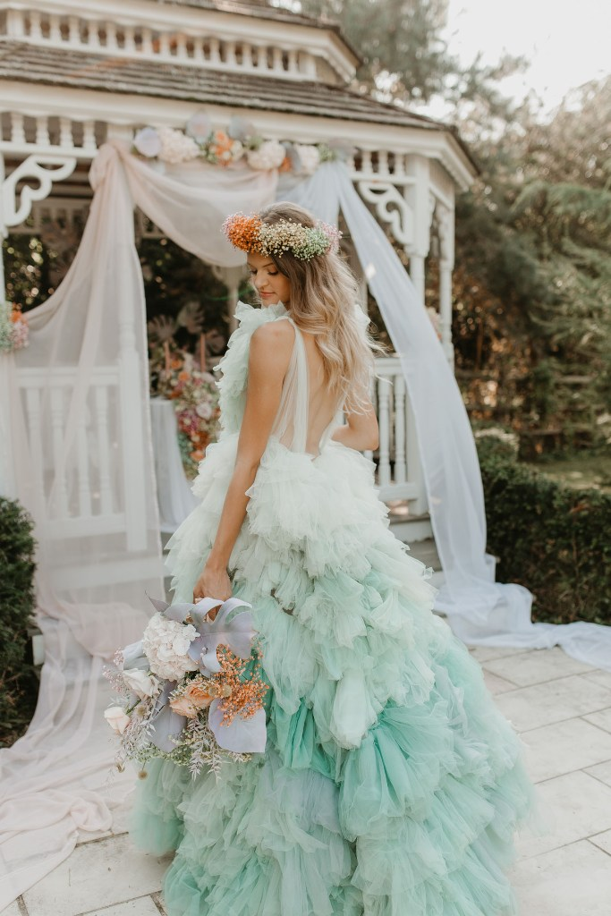 The first wedding dress was an ombre green one, with lots of ruffles, straps and a train, a colorful floral crown