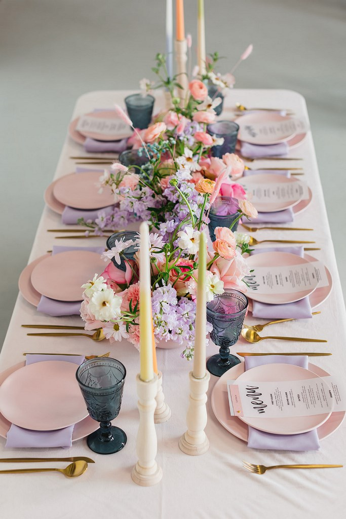 The wedding reception space was done in pastels and bold shades, with pink plates, lavender napkins, pastel candles, bright blooms and navy glasses