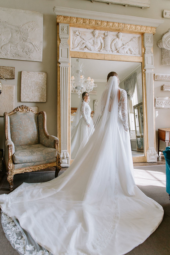 The bride was wearing a jaw-dropping high neckline A-line wedding dress with a lace bodice, a cutout back and pockets plus a cathedral veil