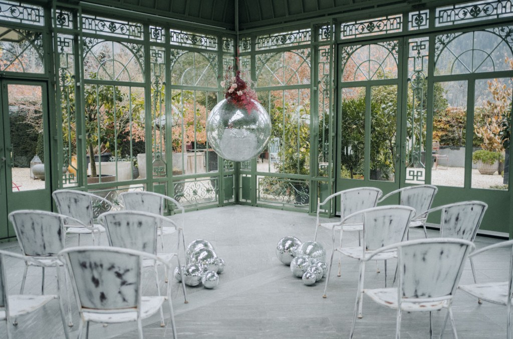 The ceremony space was done with watercolor chairs, silver disco balls on the floor and a giant one hanging