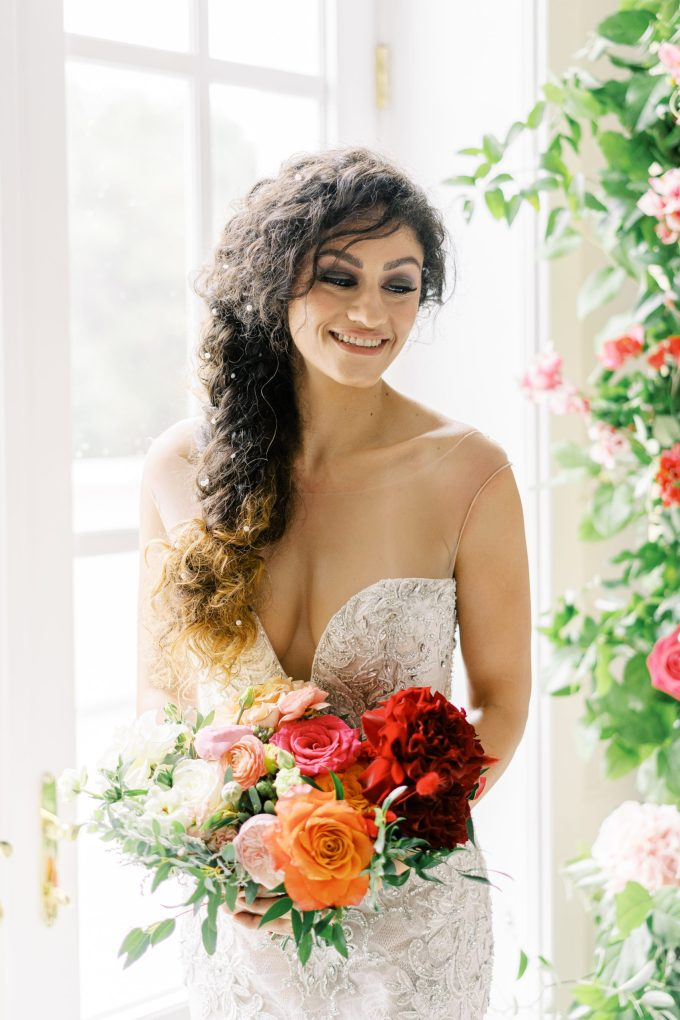 Her messy braided hair was accented with pearls and beads and she was carrying a bold wedding bouquet with greenery