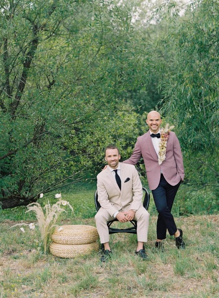 One groom was wearing a light-colored suit with a black tie and black shoes, the second groom was rocking a beautiful mauve tux, a lack bow tie, shoes and pants