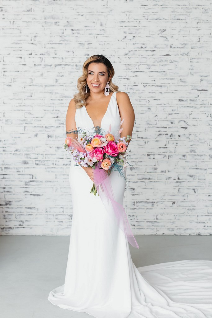 The bride was wearing a minimalist mermaid wedding dress with a covered plunging neckline and statement earrings and a train