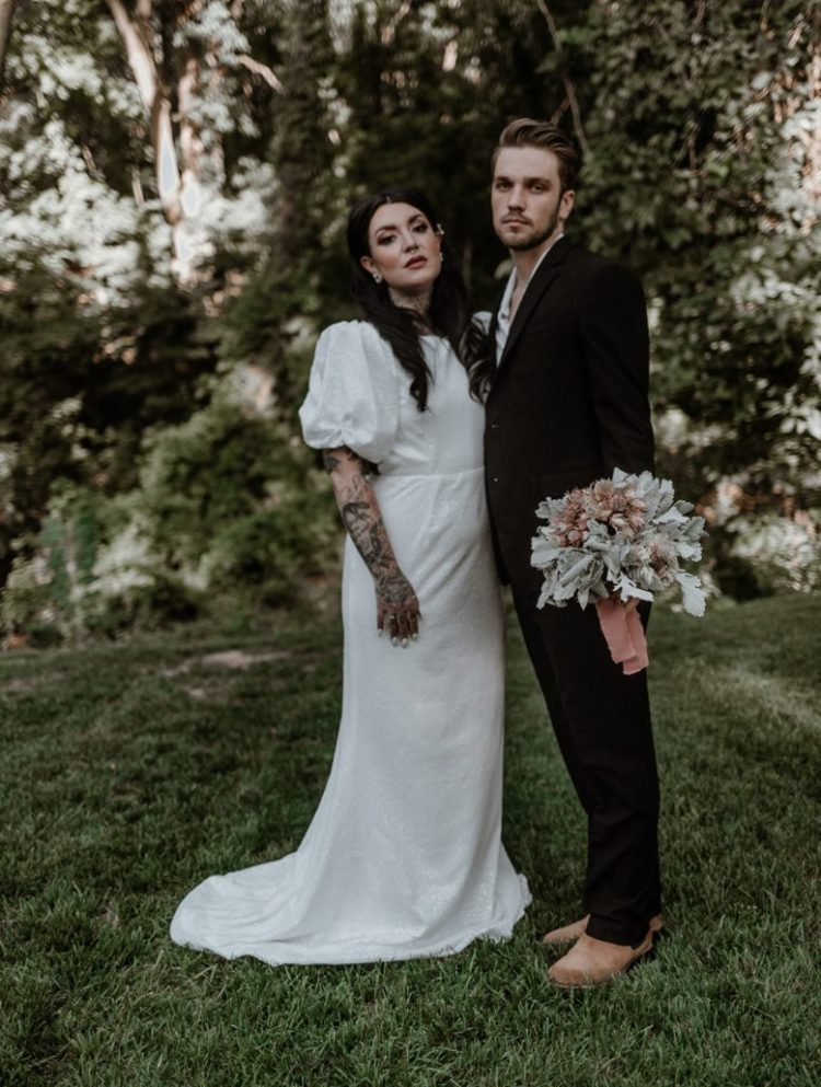 The groom was rocking a black suit, a white shirt, tan boots