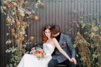 04 The groom was rocking a black turtleneck, a grey plaid blazer, black pants, shoes and grey socks, the wedding arch was done with dried blooms