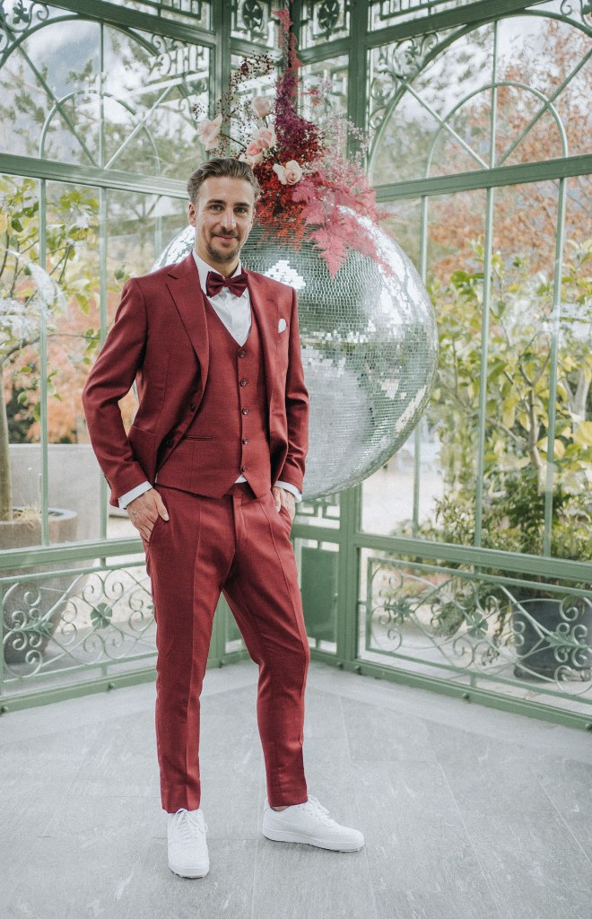 The groom was wearing a burgundy three-piece suit plus a bow tie, a white shirt and sneakers