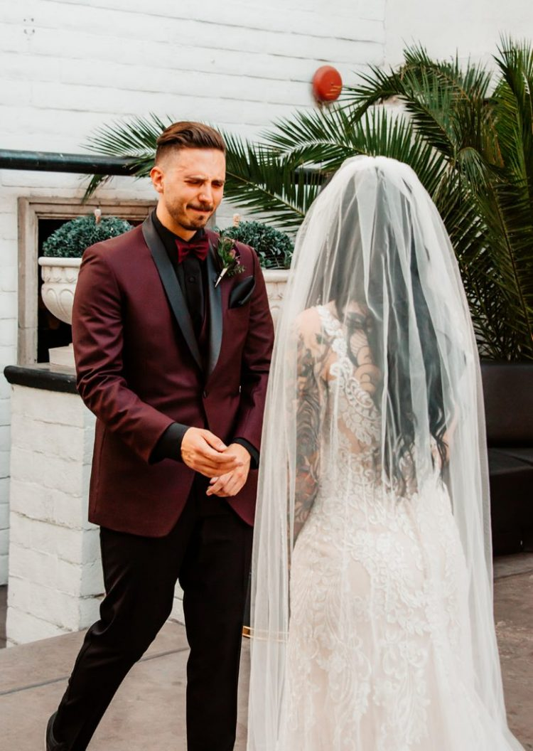 The groom was wearing a burgundy tux with a burgundy bow tie and black pants and a shirt