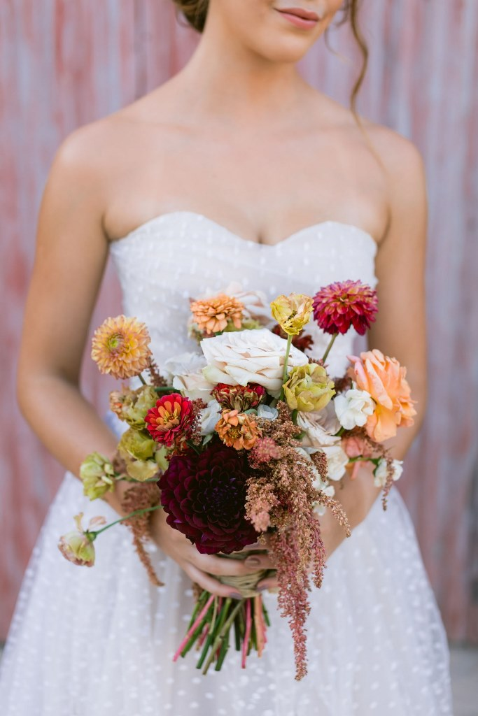 The wedding bouquet was a juxtaposition of soft pastel and neutral and dark blooms