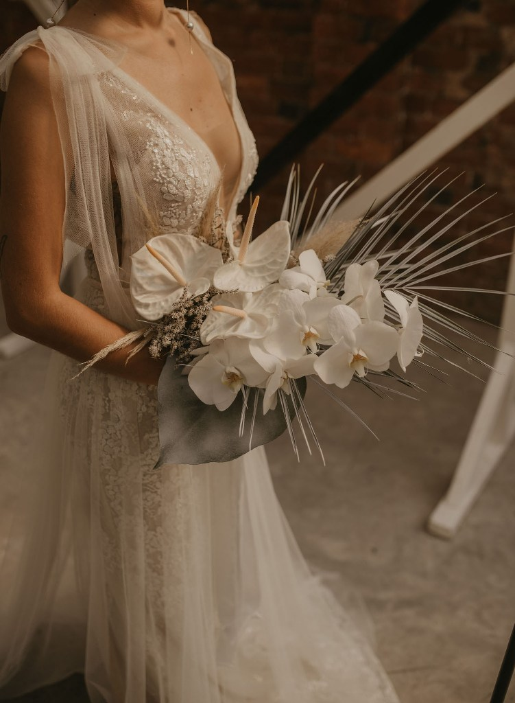 The wedding bouquet was done with catchy leaves and stylish tropical blooms