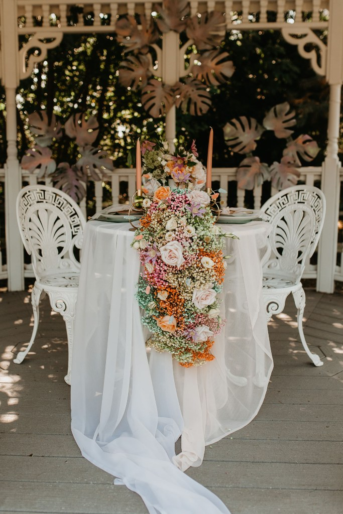 The wedding tablescape was done with neutral linens and a candy-colored floral table runner