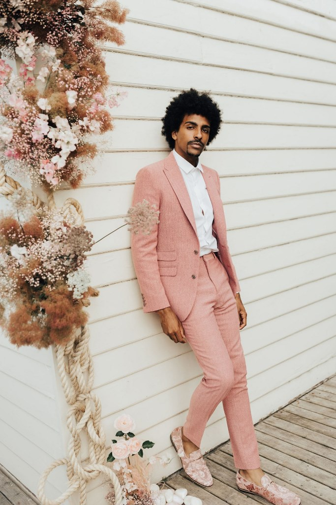 For the wedding, the groom wore a pink suit, a white shirt and floral moccasins