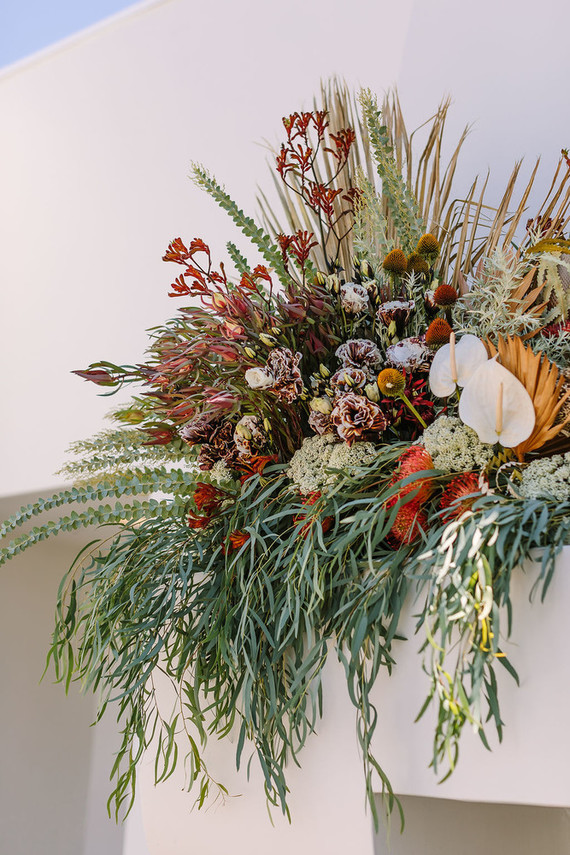 The decor was done with bold blooms, greenery and dried fronds, too