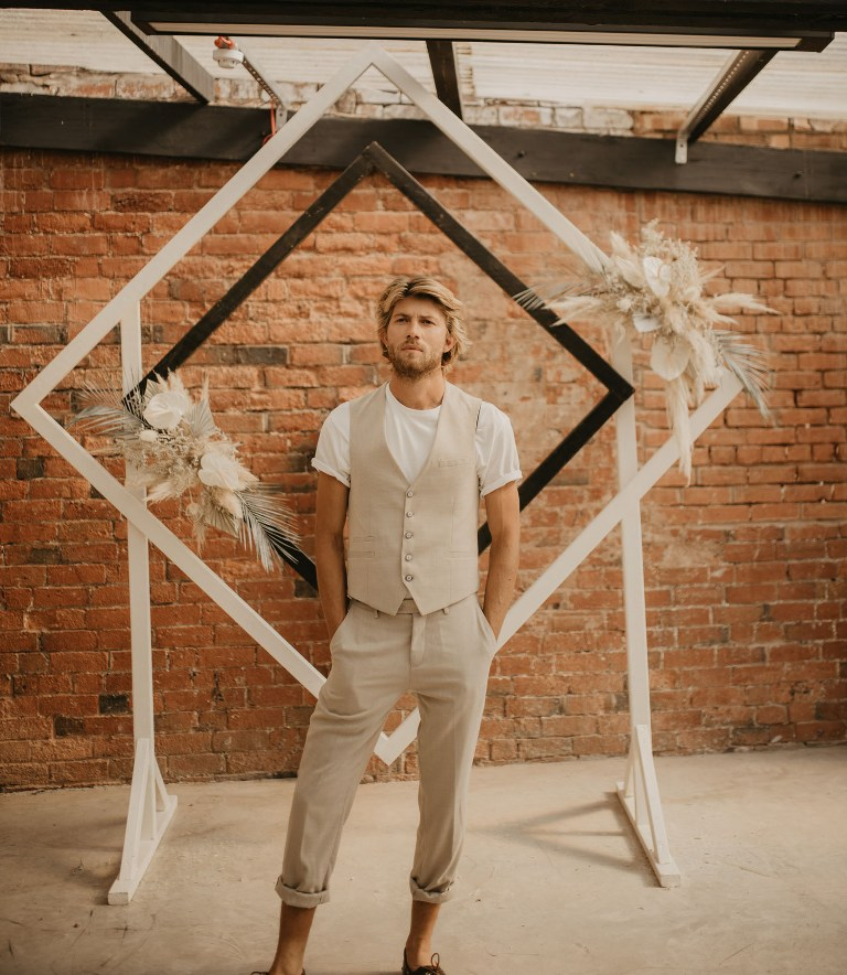 The groom was rocking a beachy look with a tan waistcoat and pants, a white tee, the wedding altar was decorated with blooms and dried fronds
