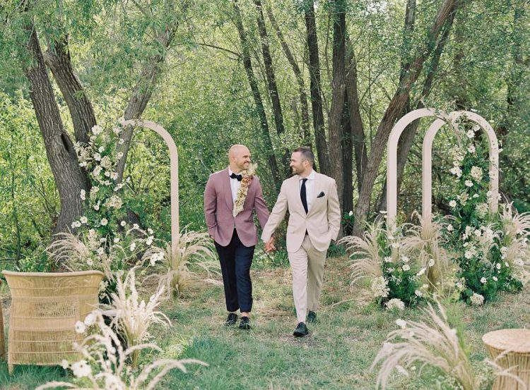 The wedding aisle was lined up with the same grasses and blooms and done with rattan chairs