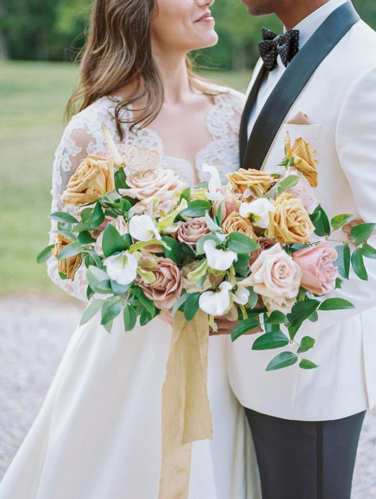 The wedding bouquet was done with blush and peachy roses and much greenery