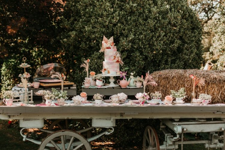 The wedding cake table was done with greenery, pastel blooms and vintage teaware