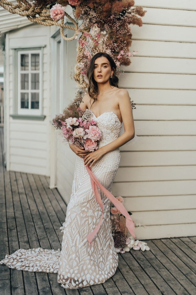The bride was wearing a strapless A-line wedding dress that looked as if covered with shells