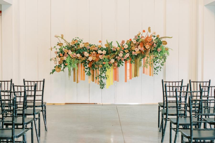 The wedding altar was done with bold fresh and dried blooms, greenery and colorful ribbons