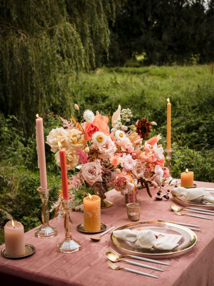 The wedding tables was laid with a mauve tablecloth, some pink blooms, colored candles and gold cutlery and chargers