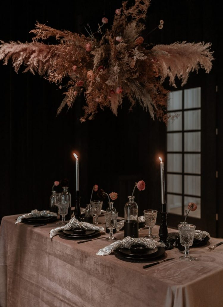 The wedding tablescape was done with a terracotta tablecloth, a dried grass and bloom overhead hanging, black candleholders and plates and silver napkins