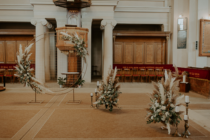 There was a round wedding arch decorated with pampas grass and neutral blooms plus leaves and matching arrangements around