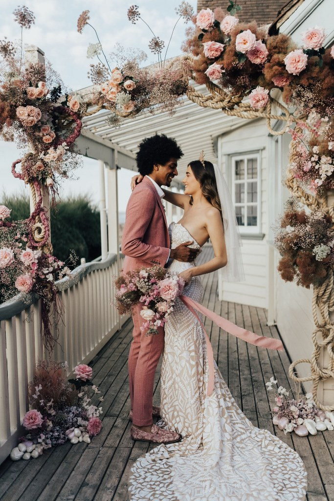 The wedding arch was done with pink blooms, dried herbs and greenery, rope, pebbles and rocks