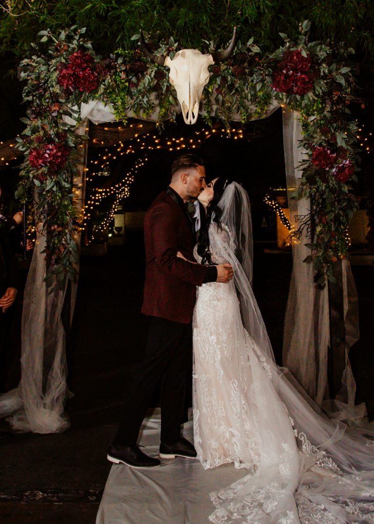 The wedding arch was done with white tulle, reenery, burgundy blooms and an animal skull