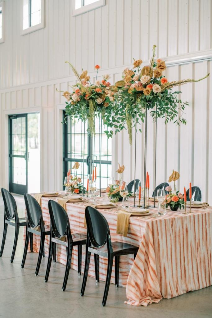 The wedding reception space was done with a bright tablecloth, a bold floral installation over the table and orange candles