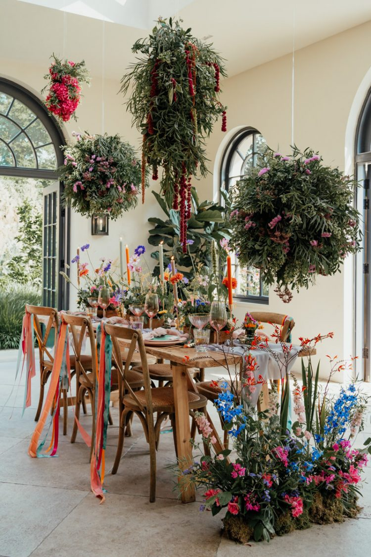The wedding reception space was done with overhead greenery and floral installations and bold blooms