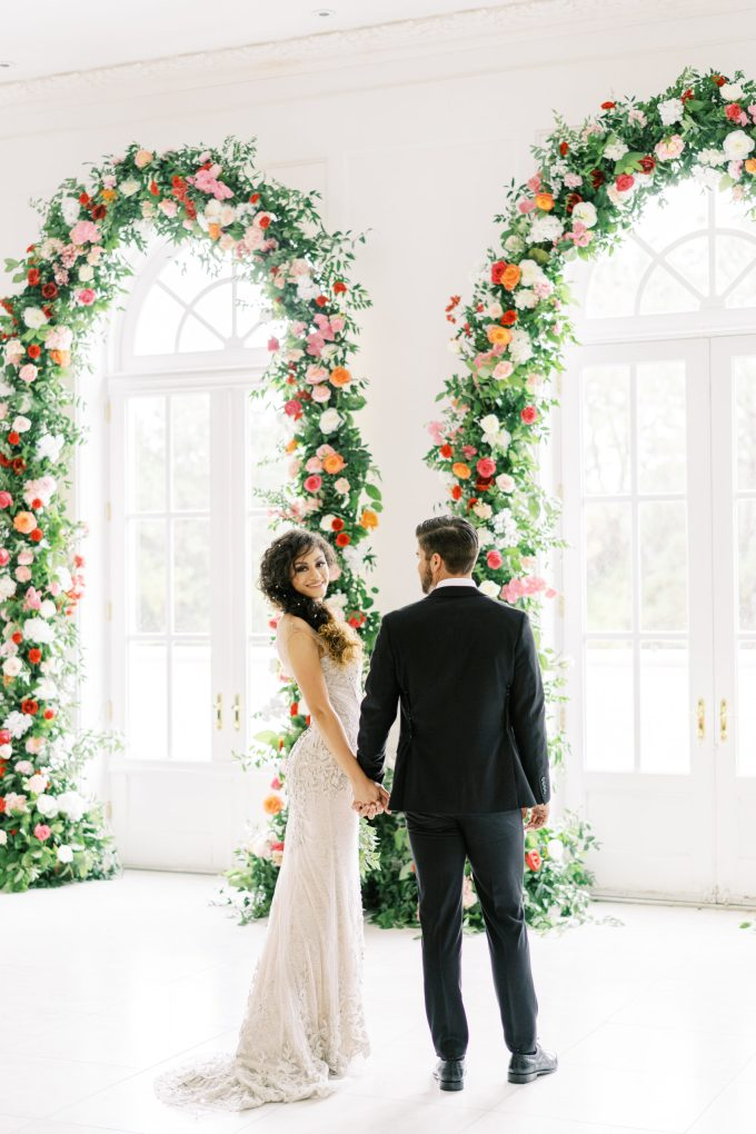 There were many floral wedding arches with bold blooms and greenery covering and French doors