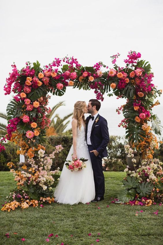 a gradient wedding arch from light pink and rust, to peachy, pink and hot pink on top and again light shades on the other side