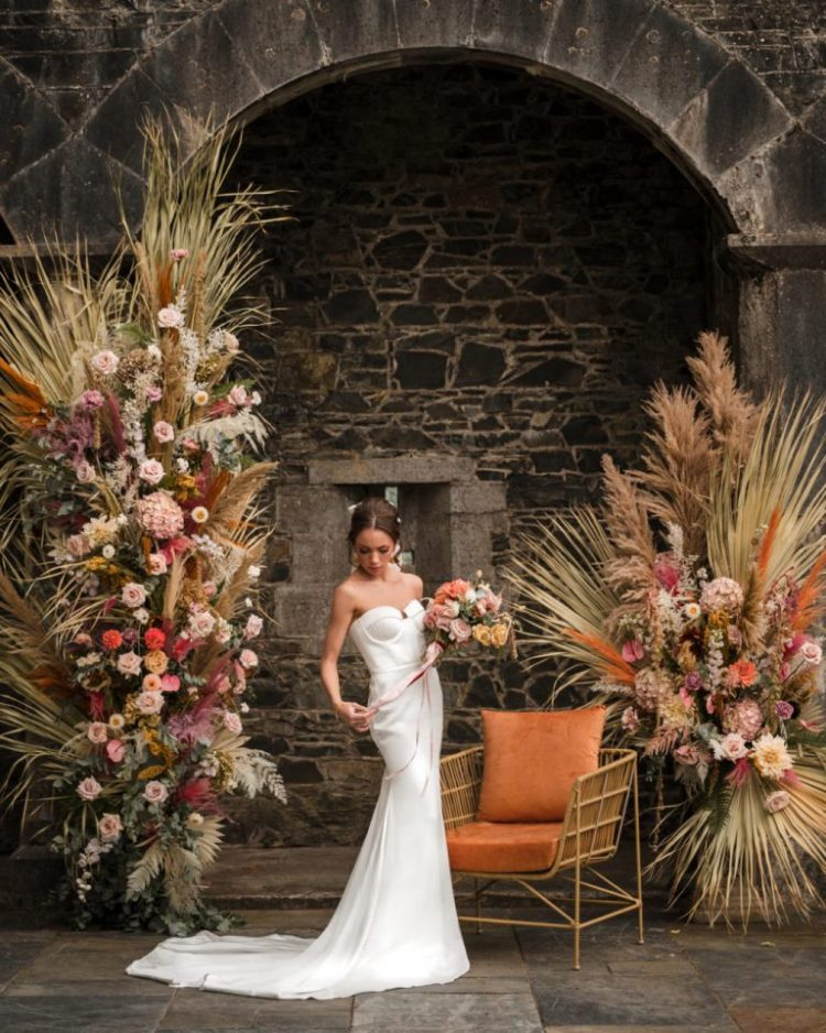 The wedding altar was jaw-dropping, with bold and pastle blooms, dried fronds and leaves