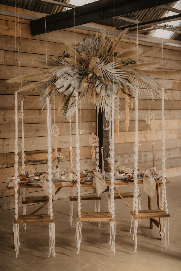 The wedding reception was done with swings instead of chairs, an overhead leaf and pampas grass installation