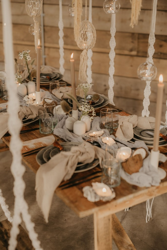 Grey linens and plates, neutral candles, blooms and grasses created a very beachy tablescape