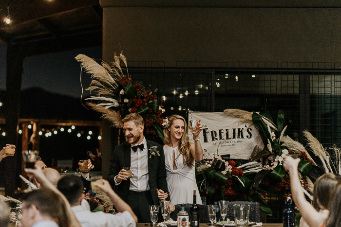 Lush red and blush floral arrangements, pampas grass, fancy signs and decor were created for the venue