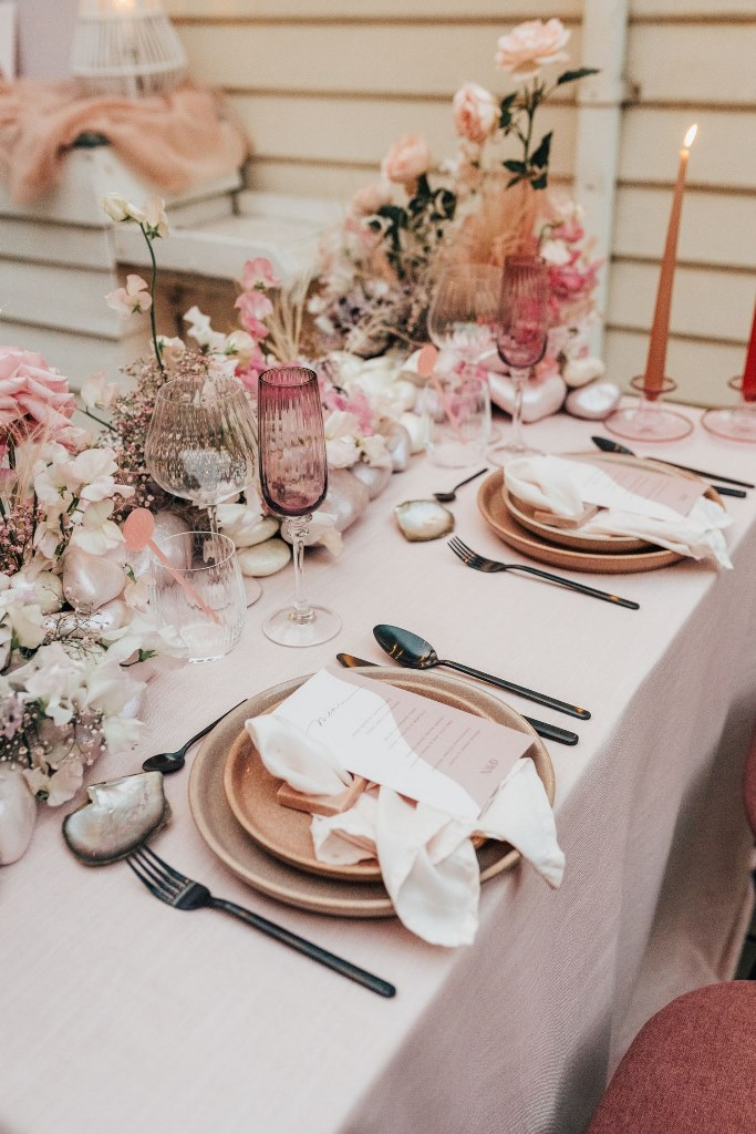 The table was decorated with mother of pearl, shells, pink porcelain, glasses and blooms