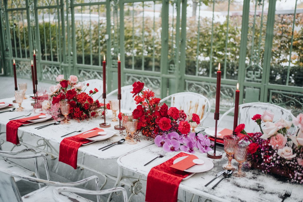 The wedding tablescape was done with hot pink and red blooms, red candles nd napkins, color block stationery and pink glasses
