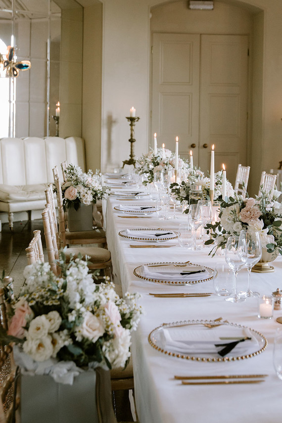 The wedding tablescapes were done with blush and neutral blooms and greenery, elegant cutlery and chargers