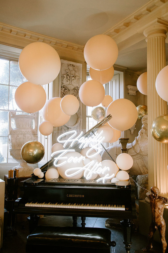 A piano decorated with balloons and a neon signs feels very party-like
