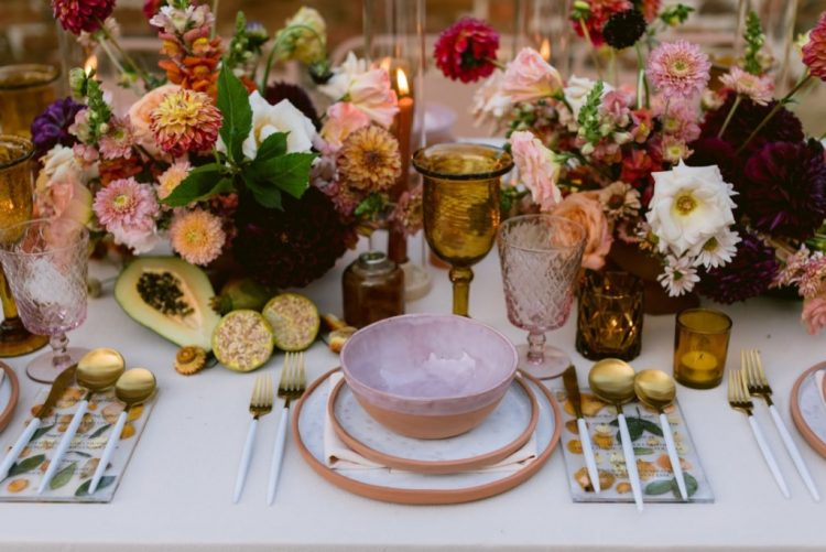 The reception table showed off lush florals, fruits, candles for decor and lovely printed plates and bowls