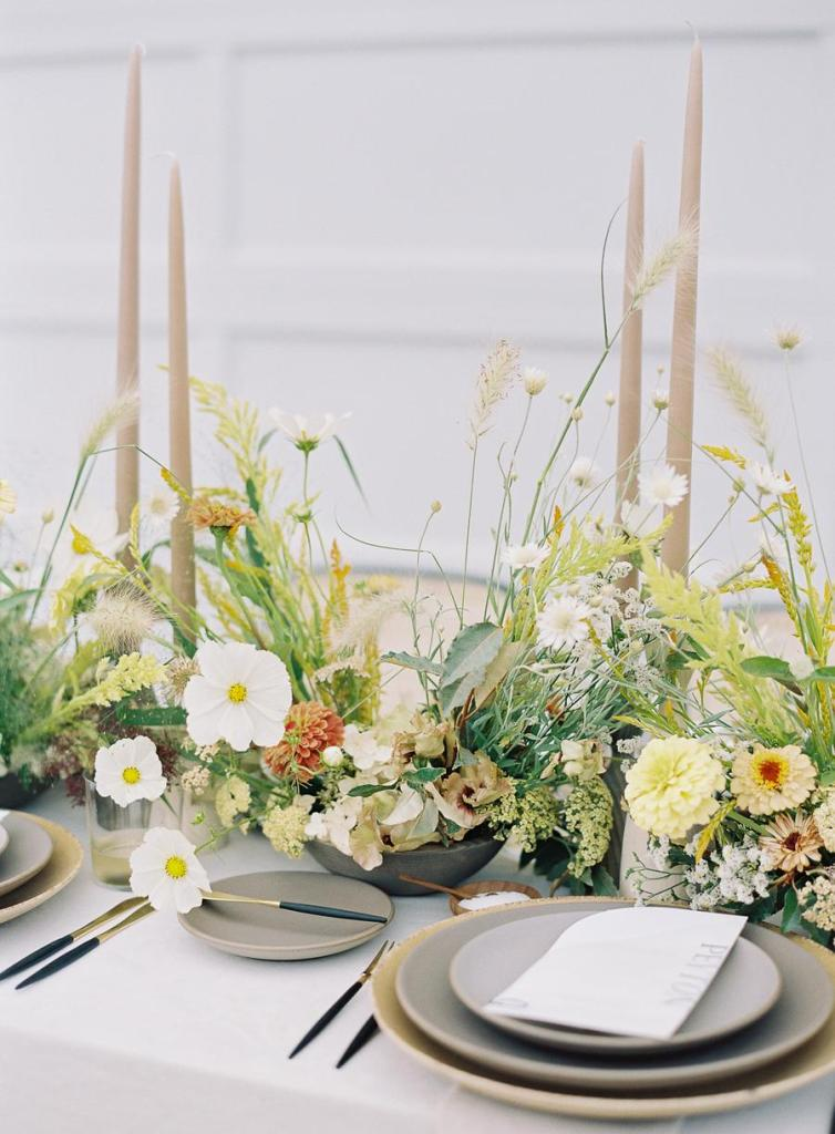 The wedding tablescape was done with bright and neutral blooms, pastel candles and grey porcelain
